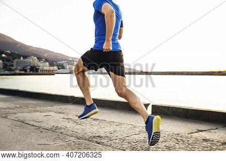 Back Male Runner Run In Morning Along Sea Embankment In City