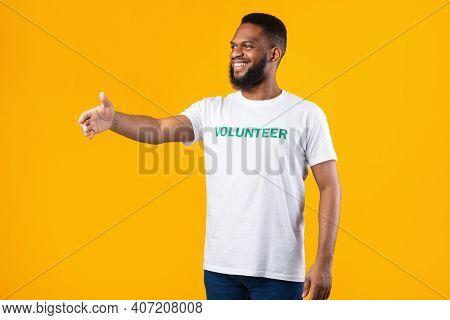 Side-view Of African Volunteer Man Offering Hand For Handshake Greeting Standing Over Yellow Studio