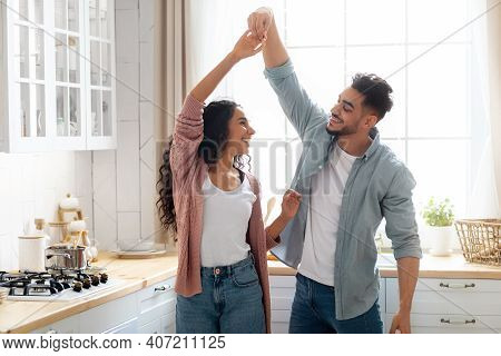 Romantic Arab Spouses Dancing In Kitchen Interior, Having Fun At Home, Modern Muslim Couple Holding