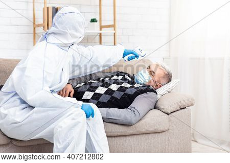 Urgent Help To Old Man During Covid-19 Epidemic. Medical Worker In Hazmat Suit Examines Patient And