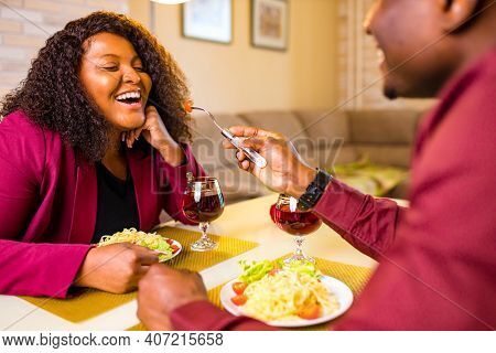 African American Couple In Love Drinking Wine From Glasses And Eating Italian Pasta In Living Room 1