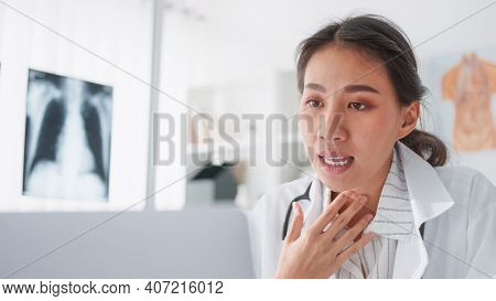 Asian Female Doctor Using Laptop Computer Online Video Call Remote Talking To Patient, Prescribe Med
