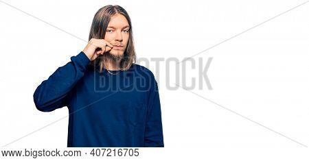 Handsome caucasian man with long hair wearing casual winter sweater mouth and lips shut as zip with fingers. secret and silent, taboo talking