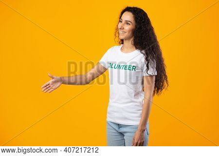 Side View Of Volunteer Lady Stretching Hand For Handshake Greeting Aside Posing Standing Over Yellow