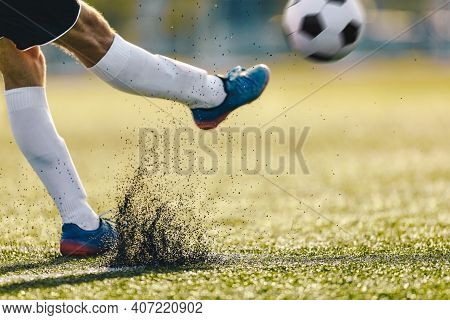 Adult Soccer Player Kicking Ball On Sunny Day On Artificial Football Pitch. Closeup Image Of Footbal