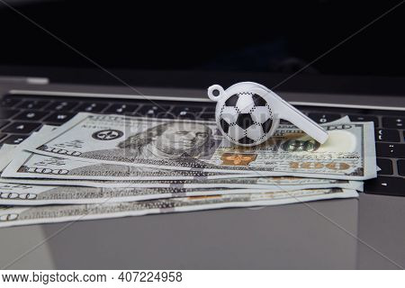 Soccer Whistle And Dollar Banknotes On Laptop. Betting On Sport Online Concept