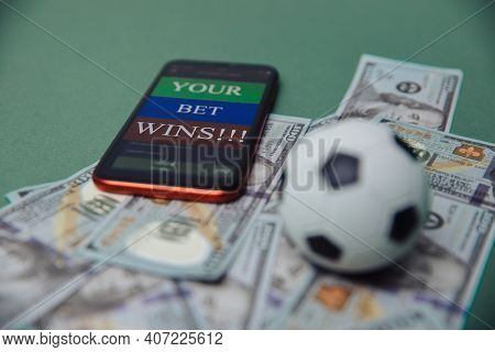 Football Business Concept. Ball And Smartphone With Bet Application On Dollar Bills And Green Backgr