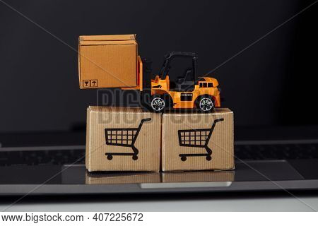 Toy Forklift With Carton Boxes On Laptop. Logistics And Wholesale Concept