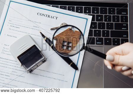Keys With Wooden House, Magnifying Glass And Contract On A Laptop. Concept Of Rent, Search Or Mortga