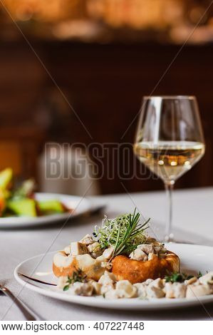 Stuffed Mushrooms Filled With Cheese, Mushroom Stem And Microgreen On The White Plate With A Glass O