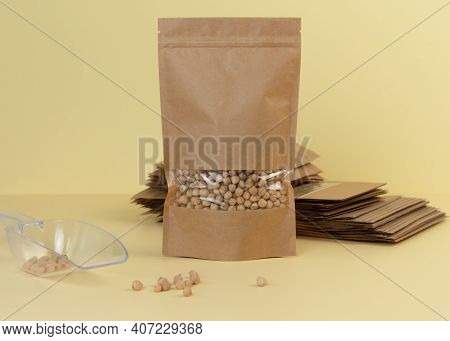 Brown Kraft Paper Doypack Bags With Groceries Front View On A Yellow Background. Packaging For Foods