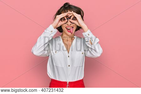 Young hispanic woman wearing business style and glasses doing ok gesture like binoculars sticking tongue out, eyes looking through fingers. crazy expression.