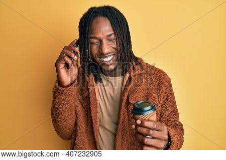 African american man with braids having conversation talking on the smartphone smiling and laughing hard out loud because funny crazy joke.