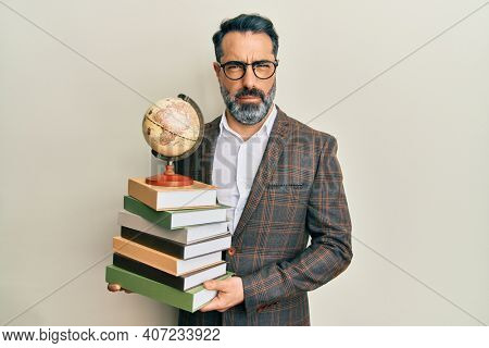 Middle age man with beard and grey hair teacher holding vintage world ball skeptic and nervous, frowning upset because of problem. negative person.