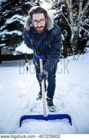 Man Shoveling Snow From A Sidewalk With A Snow Shovel.