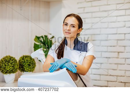 Portrait Of Young Attractive Brunette Female Doctor In Blue Medical Gloves And Uniform Posing With H