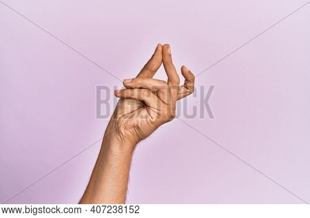 Arm and hand of caucasian young man over pink isolated background snapping fingers for success, easy and click symbol gesture with hand