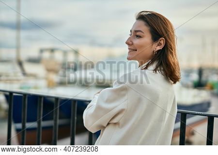 Young hispanic woman smiling happy leaning on the balustrade at the port