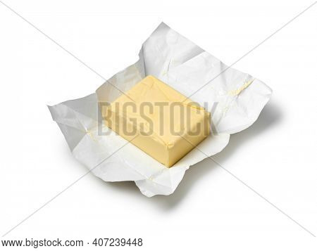 Traditional butter block unwrapped for use as a baking ingredient isolated on white background