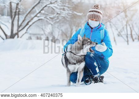 A Young Woman Using A Face Mask To Prevent The Spread Of The Coronavirus Walks With Her Dog In A Des