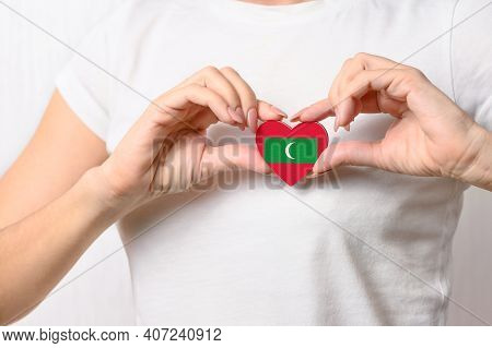 Love Maldives. The Girl Holds A Heart In The Form Of The Flag Of Maldives On Her Chest. Maldivian Pa