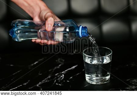 Pouring Water Into A Glass. Blue Bottle With Water. Water Pours From A Bottle Into A Glass On Black