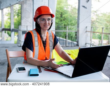 Construction Management. Woman Manager At A Construction Site. Woman In A Robot Builder Vest With A