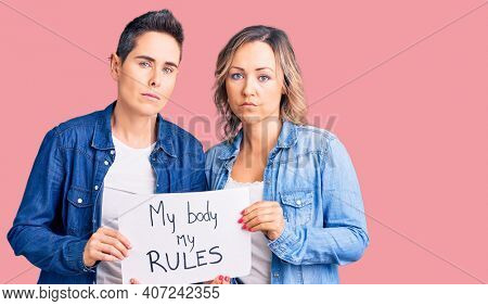 Couple of women holding my body my rules banner thinking attitude and sober expression looking self confident