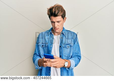 Handsome caucasian man using smartphone depressed and worry for distress, crying angry and afraid. sad expression.