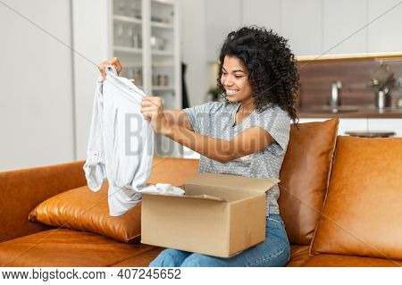 Satisfied Smiling Young African American Woman Sitting On The Sofa Opening Parcel Carton Box, Unpack