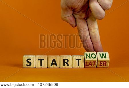 Start Now Or Later Symbol. Businessman Turns Wooden Cubes And Changes Words 'start Later' To 'start