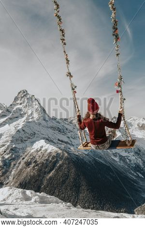 The Girl Sits On A Swing In The Mountains From The Back. Heavenly Swing Over The Abyss.