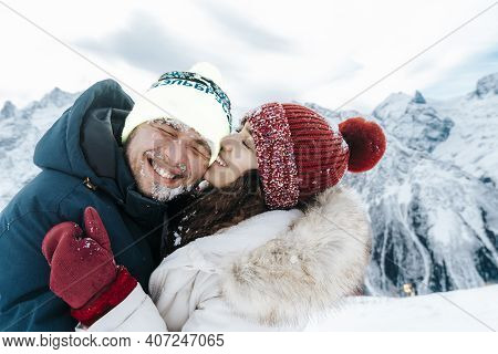Portrait Of A Happy Man And Woman In The Mountains Close-up. Husband And Wife Hugging On Vacation In