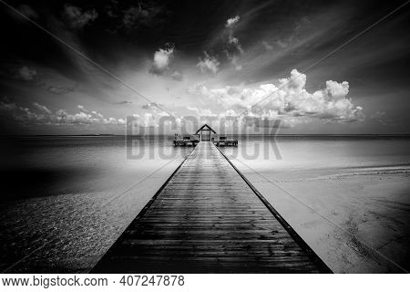 Wooden Jetty, Pier, Before Storm On The Sea. Dramatic Sky With Dark, Heavy Clouds Over Sandy Beach A