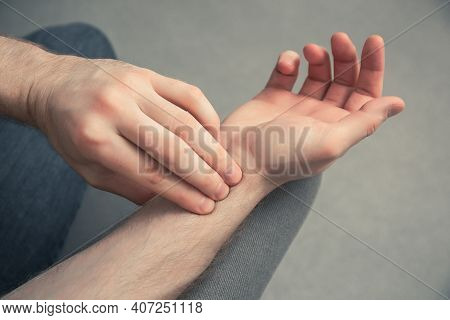 Closeup Of Man Checking His Pulse With Fingers