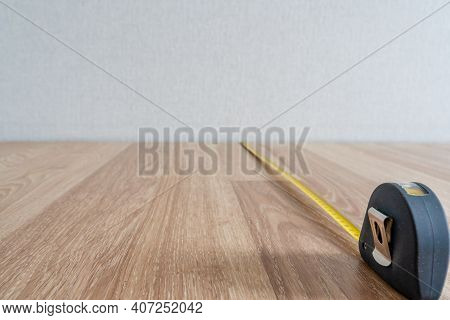 Measuring Wooden Floor With Yellow Measure Tape, Abstract Background - Out Of Focus Reconstruction A