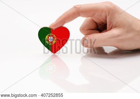 Love And Respect Portugal. A Man's Hand Holds A Heart In The Shape Of The Portugal Flag On A White G