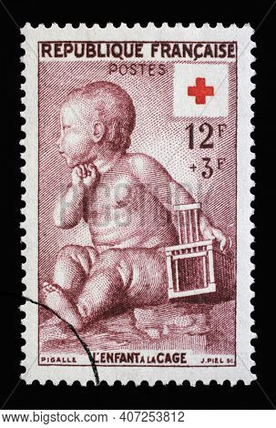 ZAGREB, CROATIA - JULY 03, 2014: Stamp printed in the France shows The child in the cage by Jean-Baptiste Pigalle, Series Red Cross, circa 1955