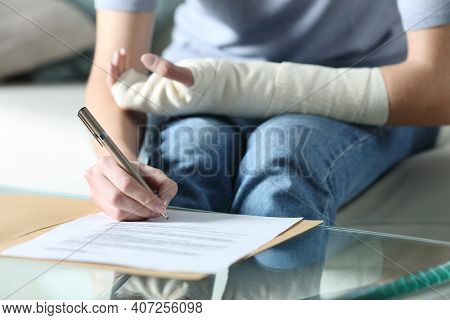 Close Up Portrait Of A Disabled Woman With Bandaged Arm Sigining Insurance Document