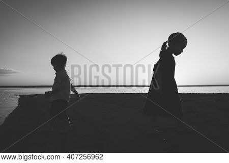 Black And White Portrait Of Two Children Leaving In Different Directions Outdoor.