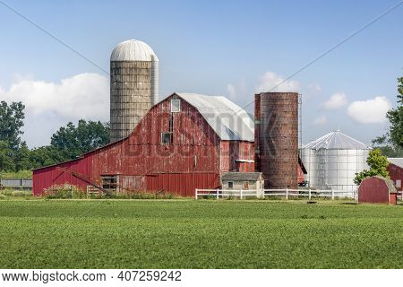 On The Other Side Of A Field Of Crops, An Old Red Barn Is Surrounded By Silos And Other Buildings An