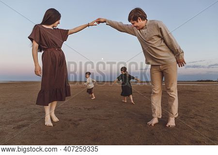 Young Parents With Two Small Children Play And Dance In The Evening On The Beach.