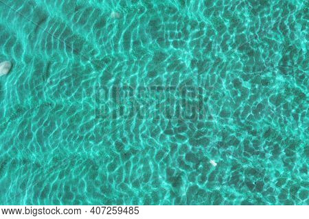 Clear Water In The Sea Texture, Sun Glare, Waves And Sea Sand At The Bottom. Light Blue Ripples Sea