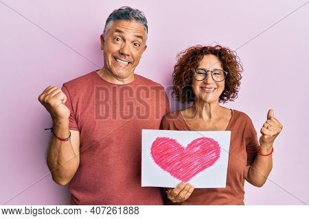 Beautiful middle age couple holding heart draw screaming proud, celebrating victory and success very excited with raised arm