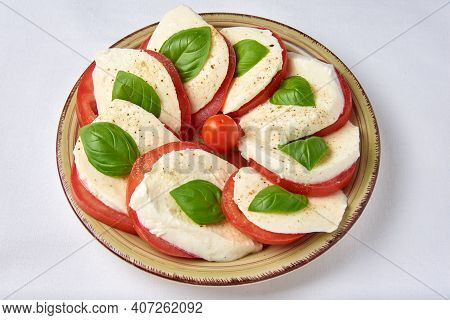 Tomatoes With Mozzarella And Basil Laid Out On A Plate