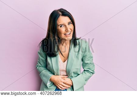 Middle age brunette woman wearing casual clothes smiling and laughing hard out loud because funny crazy joke with hands on body.