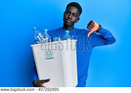 Young african american man holding recycling wastebasket with plastic bottles with angry face, negative sign showing dislike with thumbs down, rejection concept