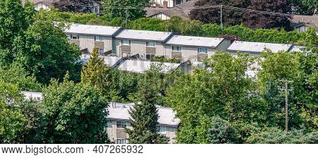 Rows Of Economic Residential Townhouses With Green Trees Around