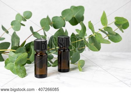 Two Amber Bottles Of Eucalyptus Essential Oil And Fresh Eucalyptus Leaves On Marble Table. Natural C