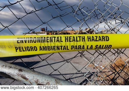 Environmental Health Hazard warning tape on a twisted chain link fence.
